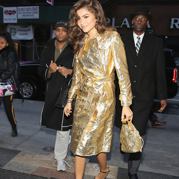 Zendaya walking in a gold trench coat