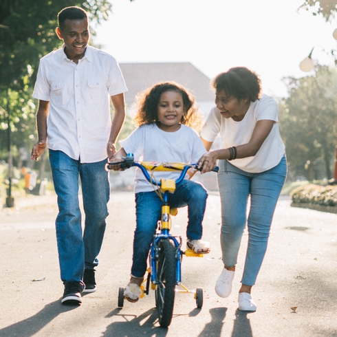 Mom and dad teach their child how to ride a two-wheel bike
