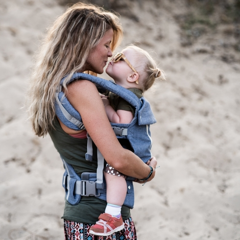 Mom stands on the beach with her baby in carrier; giving her a kiss