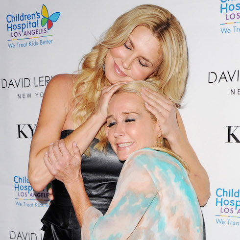 Brandi Glanville and Kim Richards hug on the red carpet