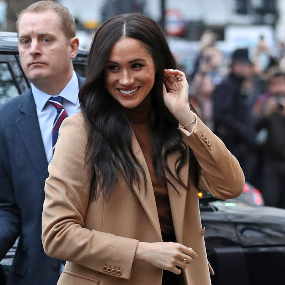 Meghan Markle in a brown trenchcoat, touches her hair and smiles at the crowd.