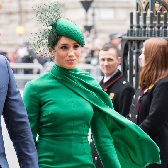 Meghan Markle wears a green dress and hat.