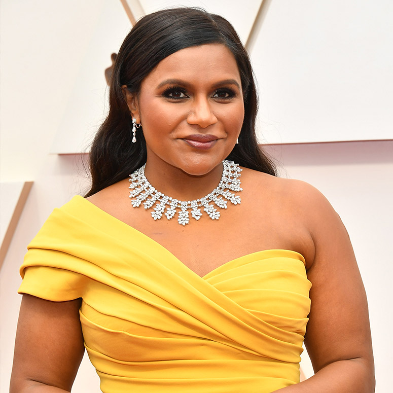 Mindy Kaling on a red carpet wearing a stunning bright yellow dress