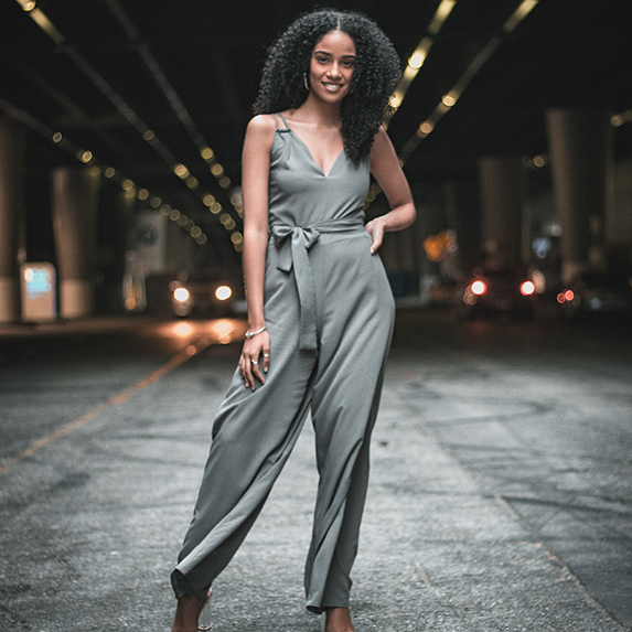A woman in a jumpsuit looking at the camera and smiling