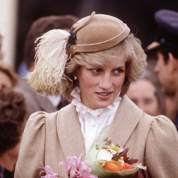 Princess Diana wears a brown hat and brown trenchcoat.