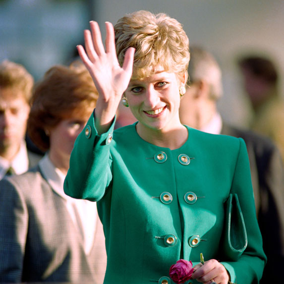 Princess Diana waves to a crowd while wearing a green, structured blazer.
