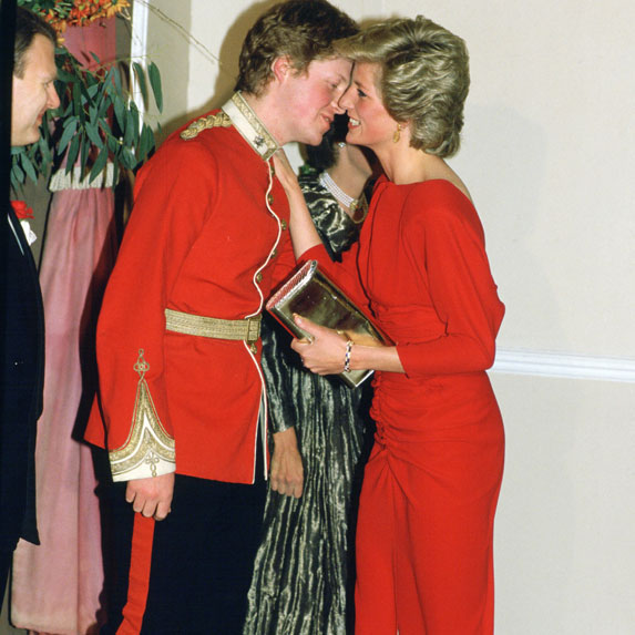 Princess Diana in a red dress gives a kiss to her son Prince Harry.