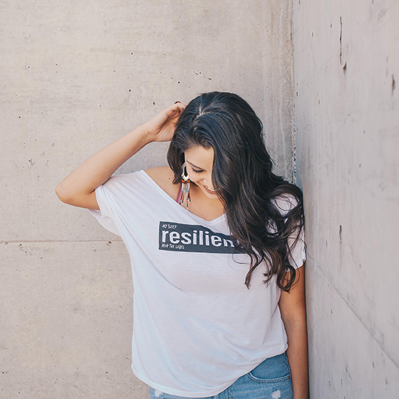 Indigenous woman in a tshirt with the word resilience written across