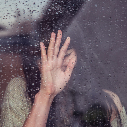 Woman putting her hand against a window on a rainy day