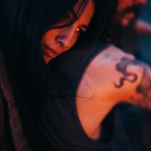 A young woman leans her head on her tattooed boyfriends shoulder while looking into the distance