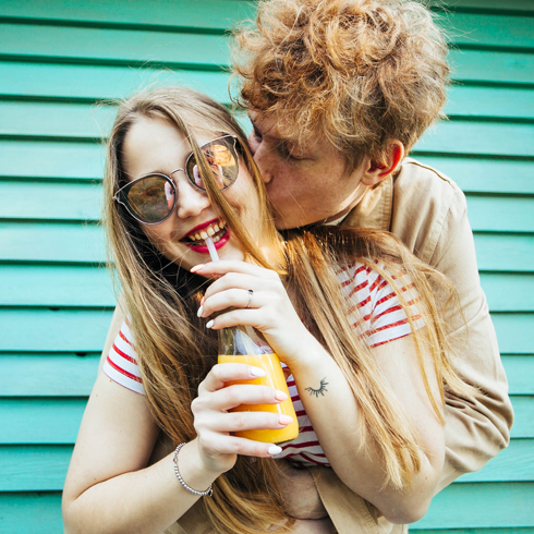 A young white heterosexual couple with the man hugging the woman from behind while she sips her drink