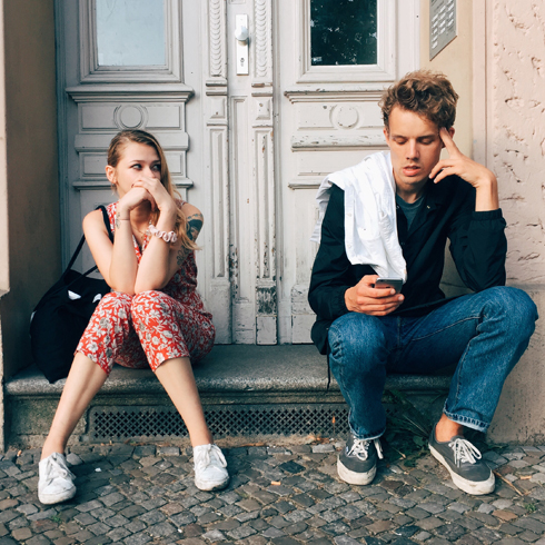 A young white heterosexual couple sitting on a door stoop, the woman watching the man as he texts someone on his phone