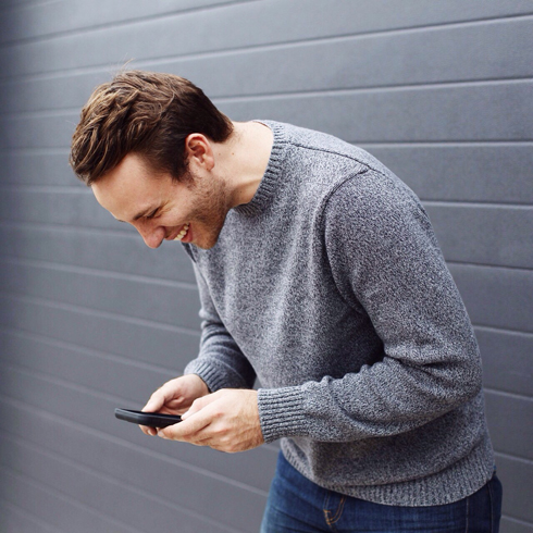 A white man hunched over with laughter looking at his phone and leaning against a brick wall