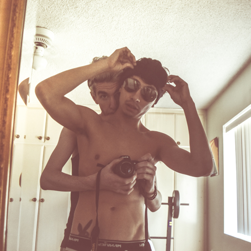 A young shirtless homosexual couple posing together in front of a mirror