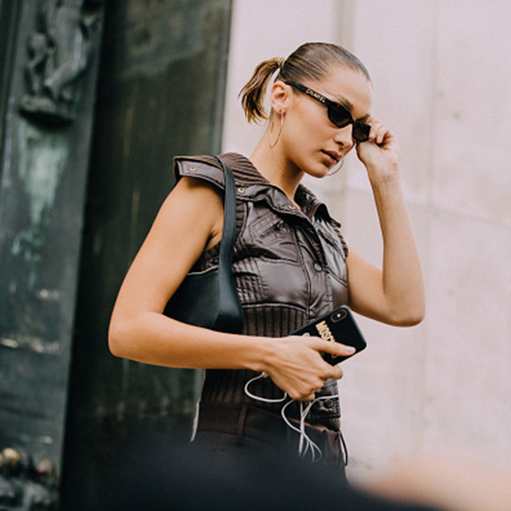 Model Bella Hadid wears black Chanel sunglasses, a small black purse, brown leather vest, and a Moschino iPhone case after the Mugler show during Paris Fashion Week
