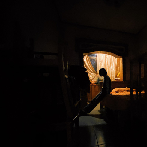 Person in a dark, distant room