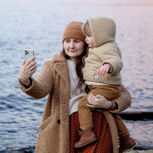 Young mom taking a selfie with their baby by the water