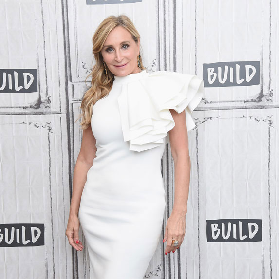 Sonja Morgan wears an elegant white dress and poses against a white wall.