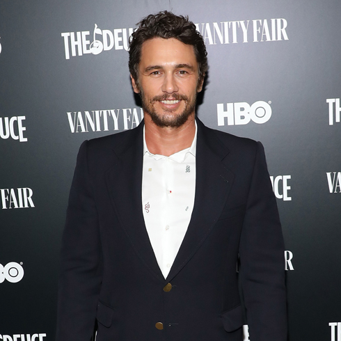 James Franco smiling in a suit and tie at a red carpet event