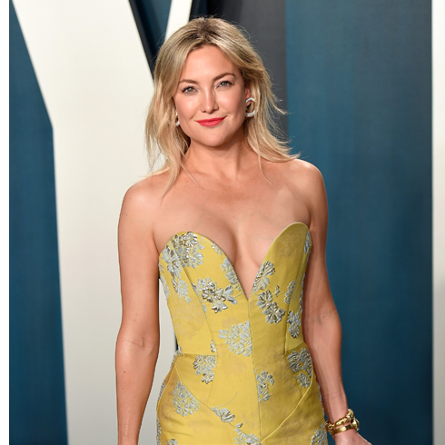 Kate Hudson poses on the red carpet in a yellow dress