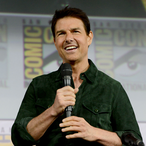 Tom Cruise holding a microphone and speaking to the audience at ComicCon