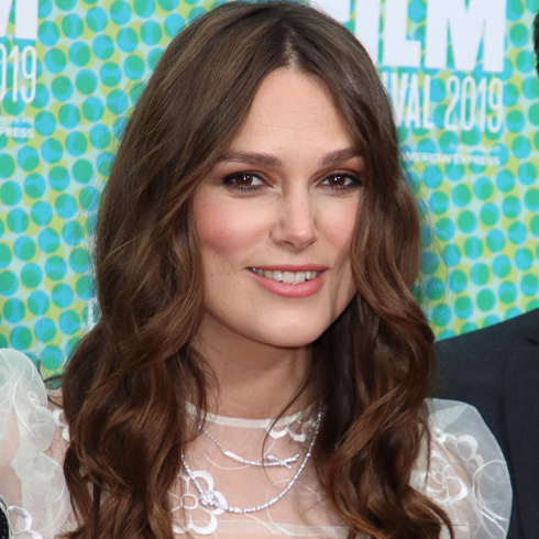 A close up of Kiera Knightley smiling for the cameras in a white dress against a blue background