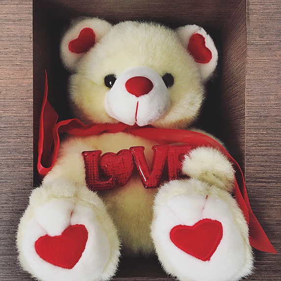 A teddy bear with harts in a box holding the words