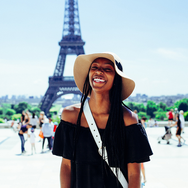 Woman standing in front of the Eiffel Tower, grinning
