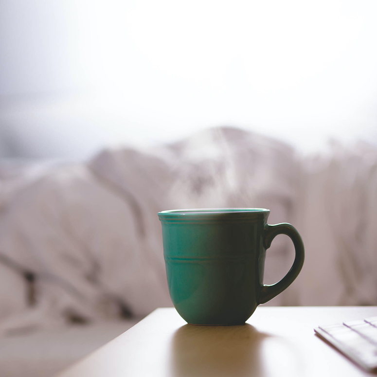 Image of a tea cup by a bedside with someone tucked away under the sheets