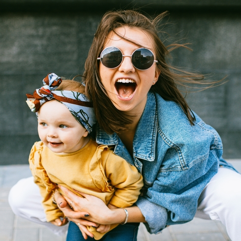 Young mom wearing sunglasses poses with her mouth open as if she is shouting with her toddler on her lap