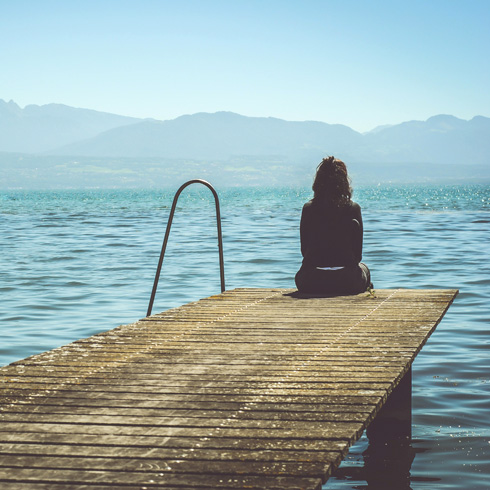 Person sitting on the end of a dock, contemplating life