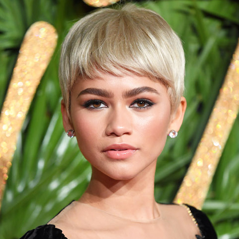 Zendaya has blonde hair against some green foliage