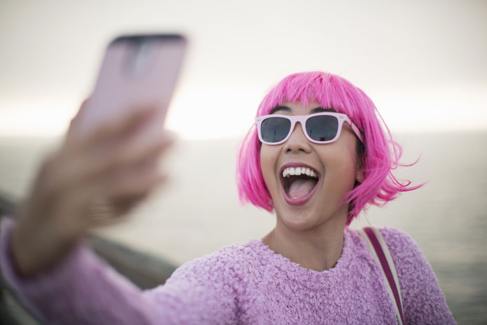 Girl with pink wig takes a selfie.