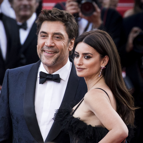 Penelope Cruz and Javier Bardem stand together on a red carpet