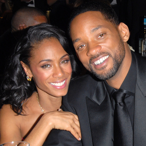 Will Smith and Jada Pinkett Smith smiling for a candid shot at an event