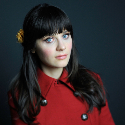 Zoey Deschanel posing for the camera in a red jacket