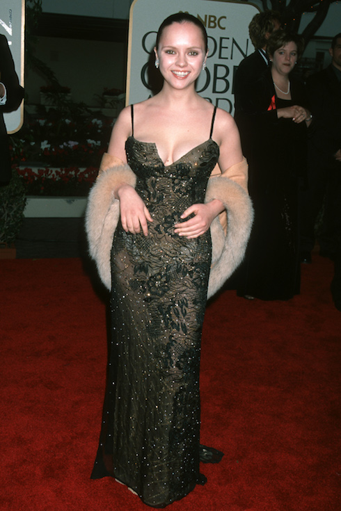 Christina Ricci smiles for photos on the Golden Globe red carpet in 1999, wearing a strappy sequin gown