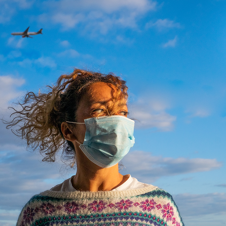Woman wearing PPE mask with airplane flying in the sky behind her