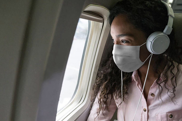 Woman with headphone on and wearing a mask looking out airplane window