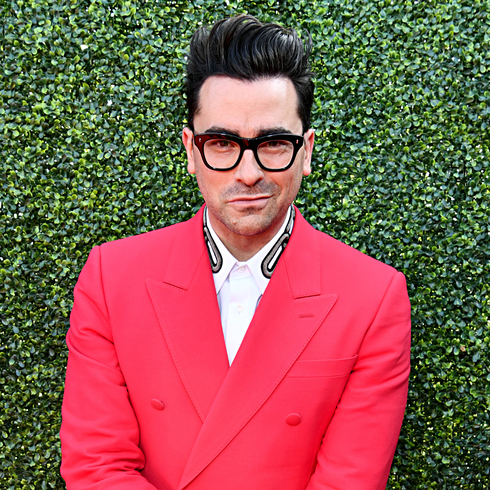 Dan Levy smiles for the camera in a bright red suit against faux grass