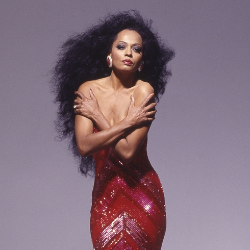 Diana Ross posing in a red dress with long hair