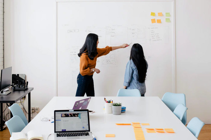 Two women in a meeting together, one points at something on a white board