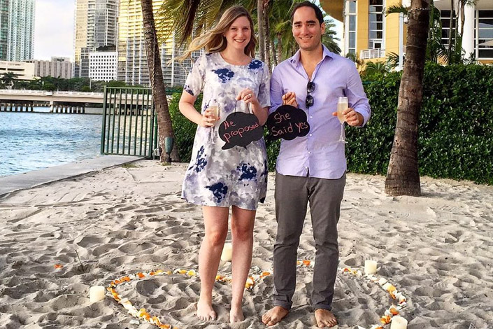 Newly engaged couple celebrate with champagne flutes and a photo on the beach