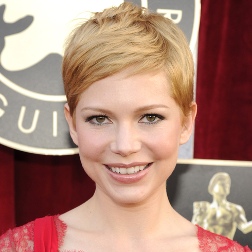 Michelle Williams with short hair, smiling on a red carpet