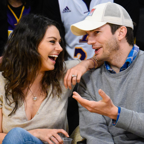 Mila Kunis and Ashton Kutcher laughing together while watching a basketball game
