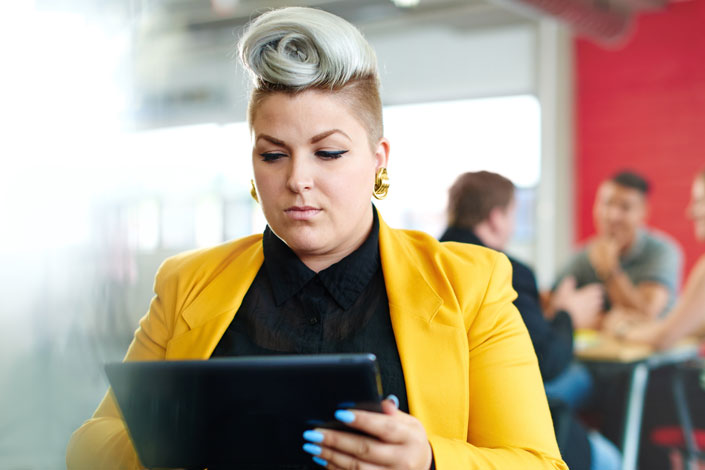 Plus size woman wears yellow blazer at work