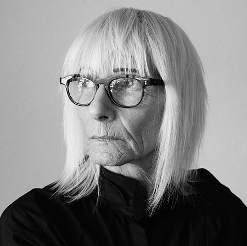 Black and white portrait of mature woman with white hair and trendy glasses looking to the side.