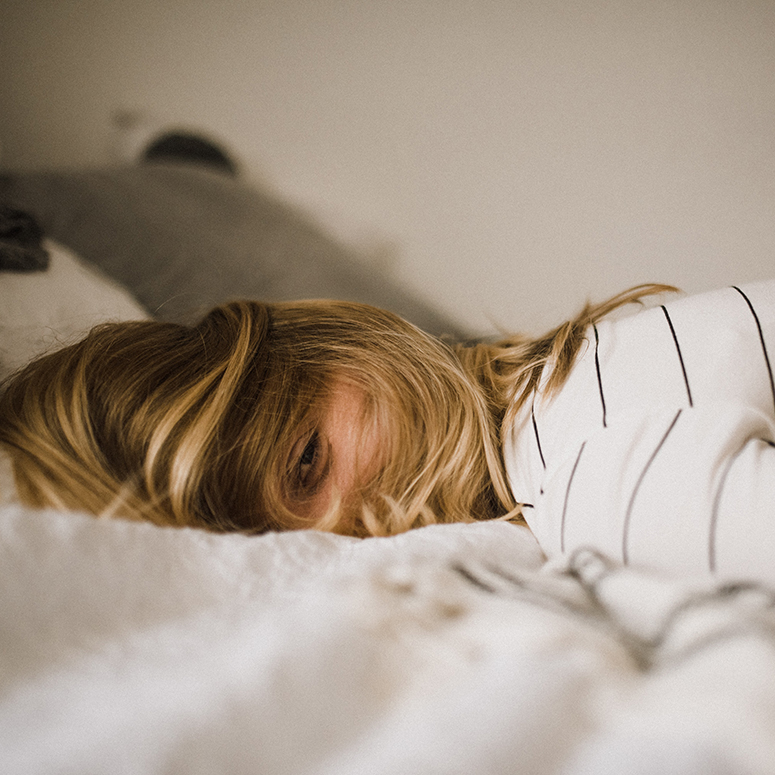 Woman on her stomach in a bed, hair disheveled and eye tiredly peeking through