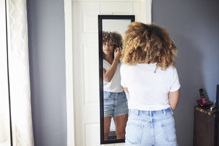 Woman with curly hair looking in the mirror
