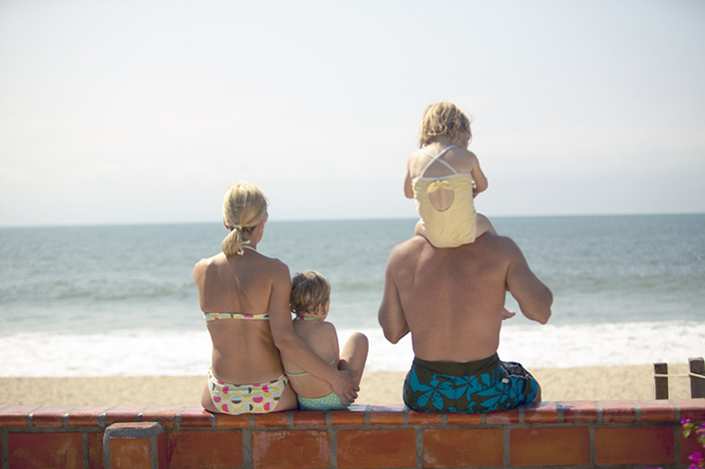 Blond, Caucasian family of four wearing bathing suits and sitting in front of the ocean.